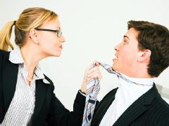 This is a photo of a woman gripping a man by his tie. It appears that she is the powerful one in the photo.