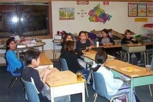 Shows young school children sitting in their classroom in the community of Nain.