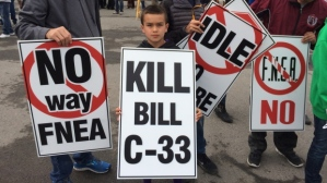 A child protests Bill C-33. Many Aboriginal leaders and community members do not agree with the bill and, despite the money that it would put into the education system, believe that it represents the Federal government having too much control over Aboriginal education.