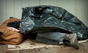 Homeless man sleeps on street using cardboard and garbage bag for blankets.